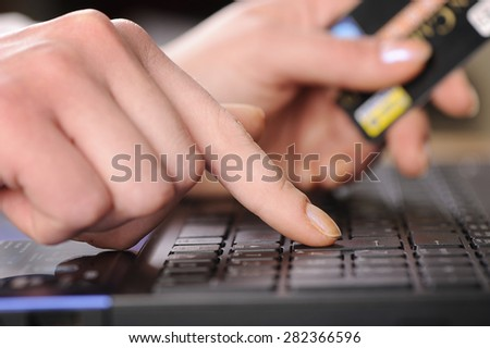 Human hands working on laptop using a credit card - stock photo