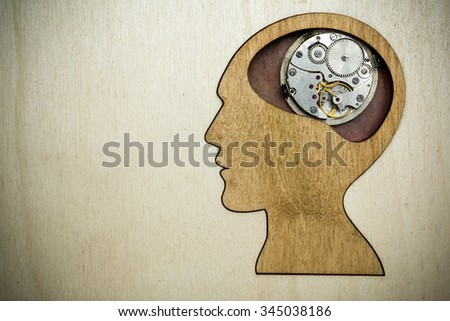 Human head silhouette with clock mechanism on the wooden background, mental health symbol