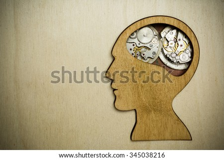Human head silhouette with clock mechanism on the wooden background, mental health symbol - stock photo