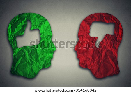 Human head with thumbs up and thumbs down symbol on gray wall background  - stock photo