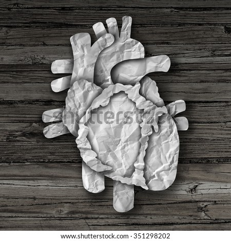 Human heart organ concept as a circulatory anatomy made of cut crumpled paper on old rustic wood as a medical health care symbol of an inner cardiovascular body part. - stock photo