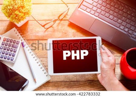 Human holding a tablet pc in hand on the desk in the morning.  PHP Concept ,Internet concept. development.