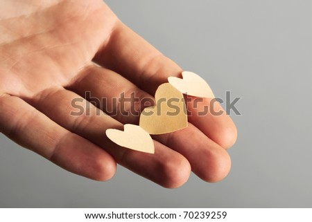 human holding little paper cutout hearts, love concept
