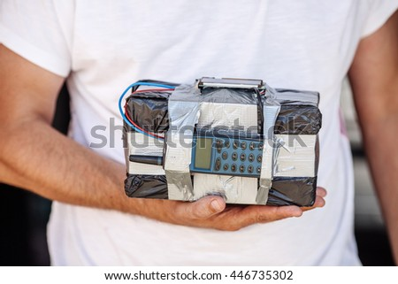 Human holding  timebomb in his hands. terrorism and dangerous life concept - stock photo