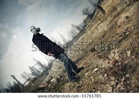 Human in the gas mask in postapoplectic landscape with toxic air. Vibrant color and moody darkness added - stock photo