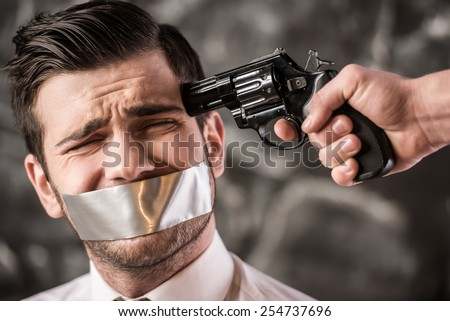 Human kidnapping. Gang member is threatening kidnapped man by pointing with gun to his head. Close-up. - stock photo