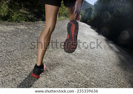 Human legs in the road warming ready for jog, run or jump - stock photo