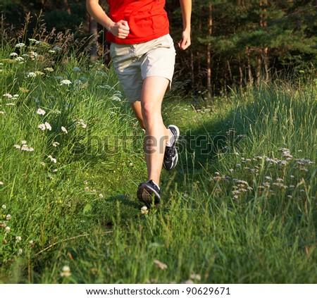 Human legs running in the green field - stock photo
