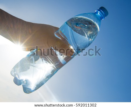 Human man's hand holding plastic transparent bottle of water against blue sky with sun rays. sunlight. sunbeam.
