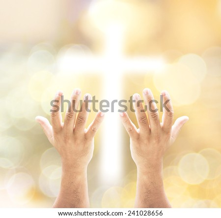 Human open empty hands with palms up, over blurred the cross and bokeh on night background. - stock photo
