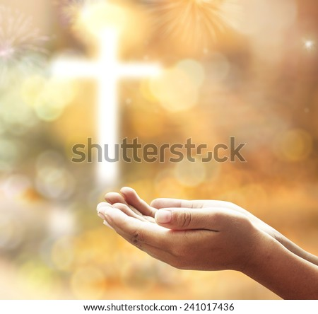 Human open empty hands with palms up, over blurred the cross with fireworks on night background. - stock photo
