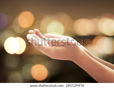 Human open empty hands with palms up over candle lights bokeh. Pray for support, Worship, Forgiveness, Mercy, Humble, Repentance, Reconcile, Adoration, Glorify, Redeemer concept. - stock photo
