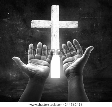 Human open empty hands with palms up, over the white cross in the dark room. - stock photo