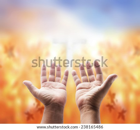 Human open hands with palms up over blurred the cross on nature background. - stock photo