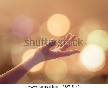 Human palm reaching upward in midst of glowing gold candle lights bokeh, candlemas: Female women empty open hand praying in warm color tone background: Pray for peace: Sunday advent: Holy spirit week - stock photo