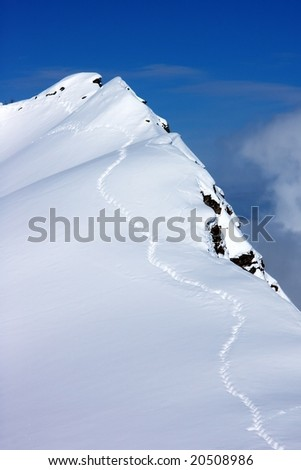 Human path on the rock edge covered by snow