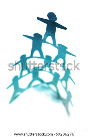 Human pyramid standing on plain background - stock photo