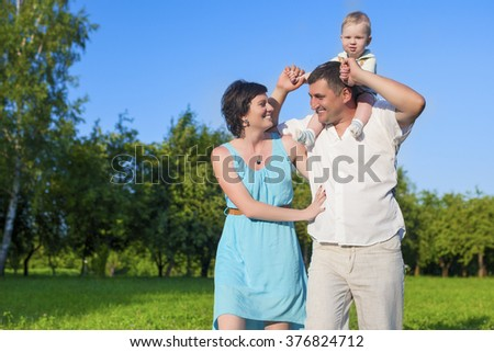 Human Relationships Concepts. Young Caucasian Family of Three People Having Good Time Together Outdoors.Horizontal Image Orientation