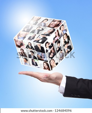 Human Resources concept: business man hand holding a magic cube made by all business people face