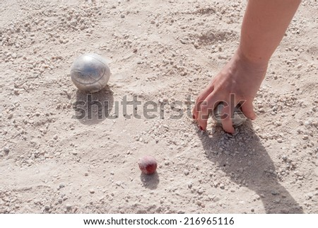 Human's hand taking a petanque ball on the ground - stock photo