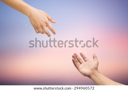 Human's hands help together on blurred twilight sky backgrounds.helping hands concept. blurred twilight backgrounds in pastel tone. - stock photo
