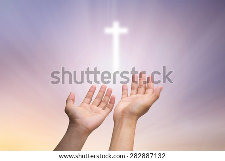 human's hands praying  cross  on blurred twilight sky background   , soft focused. - stock photo