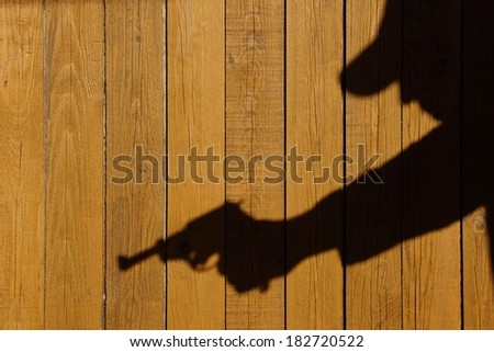 Human silhouette with handgun in shadow on wood background, with space for text or image. - stock photo