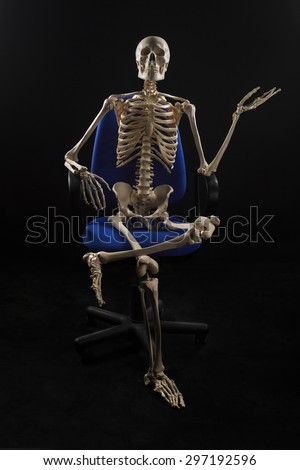Human skeletal sitting at chair, pointing with hand - stock photo