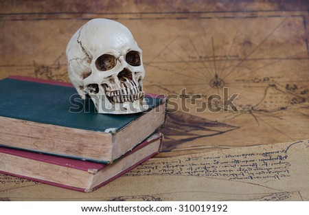 Human Skull and old text book on Old map Background - stock photo