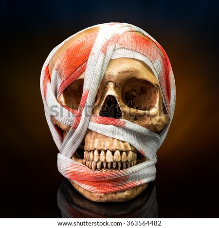 Human skull bind with blood stain bandage on dark background - stock photo