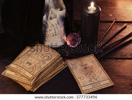 Human skull, crystal, black candle and the tarot cards on wooden table. Halloween and magic still life, fortune telling seance or black magic ritual with mysterious occult and esoteric symbols  - stock photo