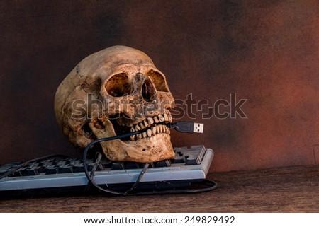 Human skull with keyboard, still life - stock photo