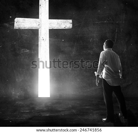 Human standing over the white cross in dark room. Worship, Forgiveness, Mercy, Humble, Repentance, Reconcile, Adoration, Glorify, Redeemer, Redemption, Pray, Praise, Way Of Life, Trust, Love concept. - stock photo