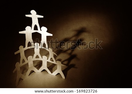 Human team pyramid on brown background. Copy space - stock photo