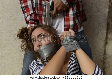 Human trafficking or kidnapping: Gang member threatening kidnapped woman by pointing with gun to her head - stock photo