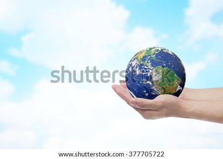 humans hand open palms gesture holding the world over blurred blue sky and clouds backgrounds :hands healing world life concept,ecology concept.environment day.Elements of this image furnished by NASA - stock photo