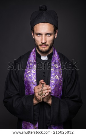 Humble priest with Christian Cross. Studio portrait on black background - stock photo