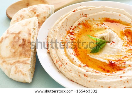 hummus dip plate and lemon on wooden table  - stock photo