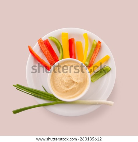 Hummus with capsicum and green onion over circular plate on pink background. Funny style. - stock photo