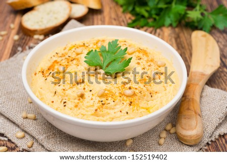 Hummus with pine nuts in a bowl - stock photo