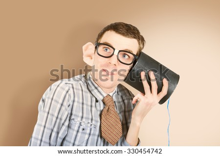 Humor styled portrait of a funny business man with big ears listening intently to customer on retro toy phone. We hEar you - stock photo