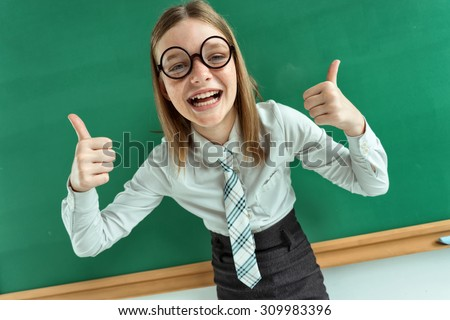 Humorous high angle view of Happy young schoolgirl has her thumbs up / photo of teen school girl wearing glasses, creative concept with Back to school theme - stock photo