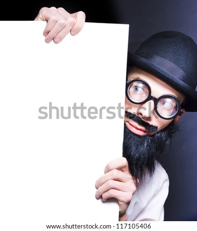 Humorous Image Of A Stereotypical Bearded Professor Wearing Glasses And A Hat Peering Inquisitively Around A Blank Copy Space Board For Your Scientific Text - stock photo