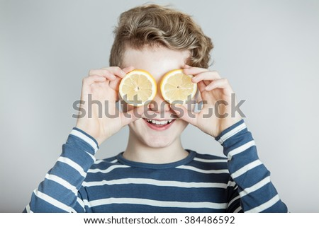 Humorous Nutrition Themed Concept Image of Smiling Boy with Wavy Blond Hair Holding Slices of Lemons Over Eyes in Studio with Gray Background and Copy Space - stock photo