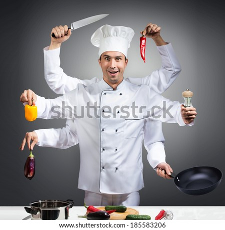 Humorous portrait of a chef with many hands on gray background - stock photo
