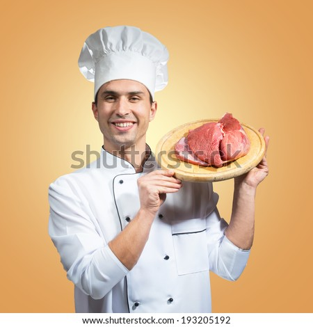 Humorous portrait of a man in chef's hat looking at piece of meat with a knife in his hand - stock photo