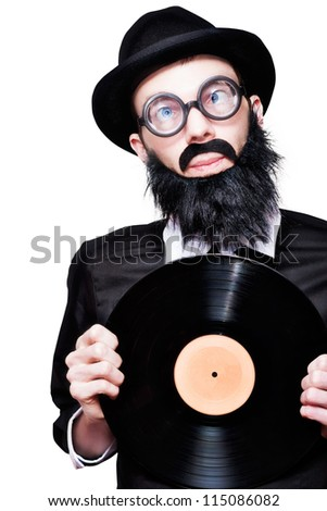 Humorous Portrait Of A Sixties Retro Rock Man With Beard Moustache And Glasses Holding Music Record Vinyl In A Depiction Of 60s Rock N Roll Music - stock photo