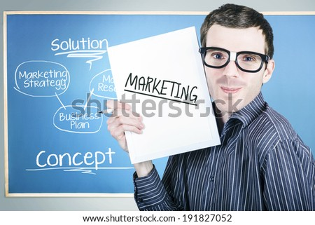 Humorous portrait of an education marketing man wearing dork glasses displaying business plan for strategy success
