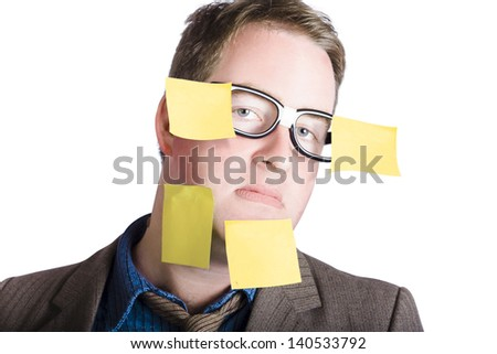 Humorous portrait of an overwhelmed man wearing dorky glasses while carrying his crazy workload on face with yellow sticky notes. Over commitment - stock photo