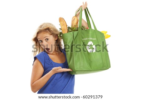 Humorous portrait of young woman with green recycled grocery bag - stock photo